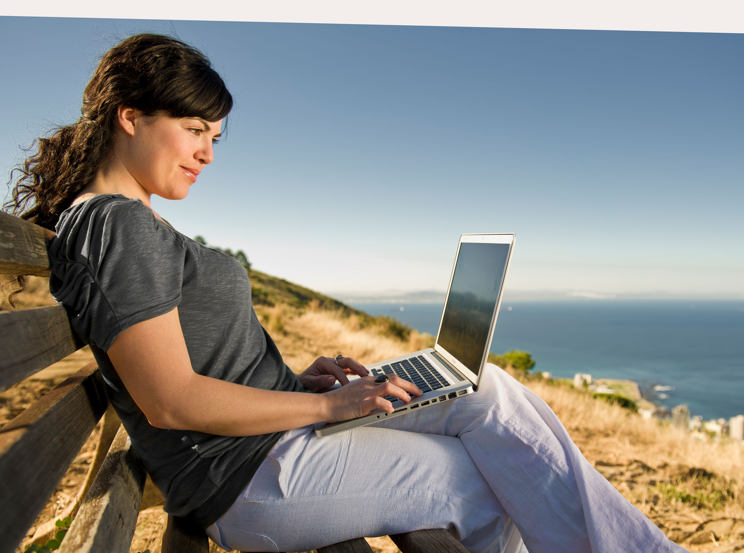 Girl sitting with her MacBook at the beach unretouched