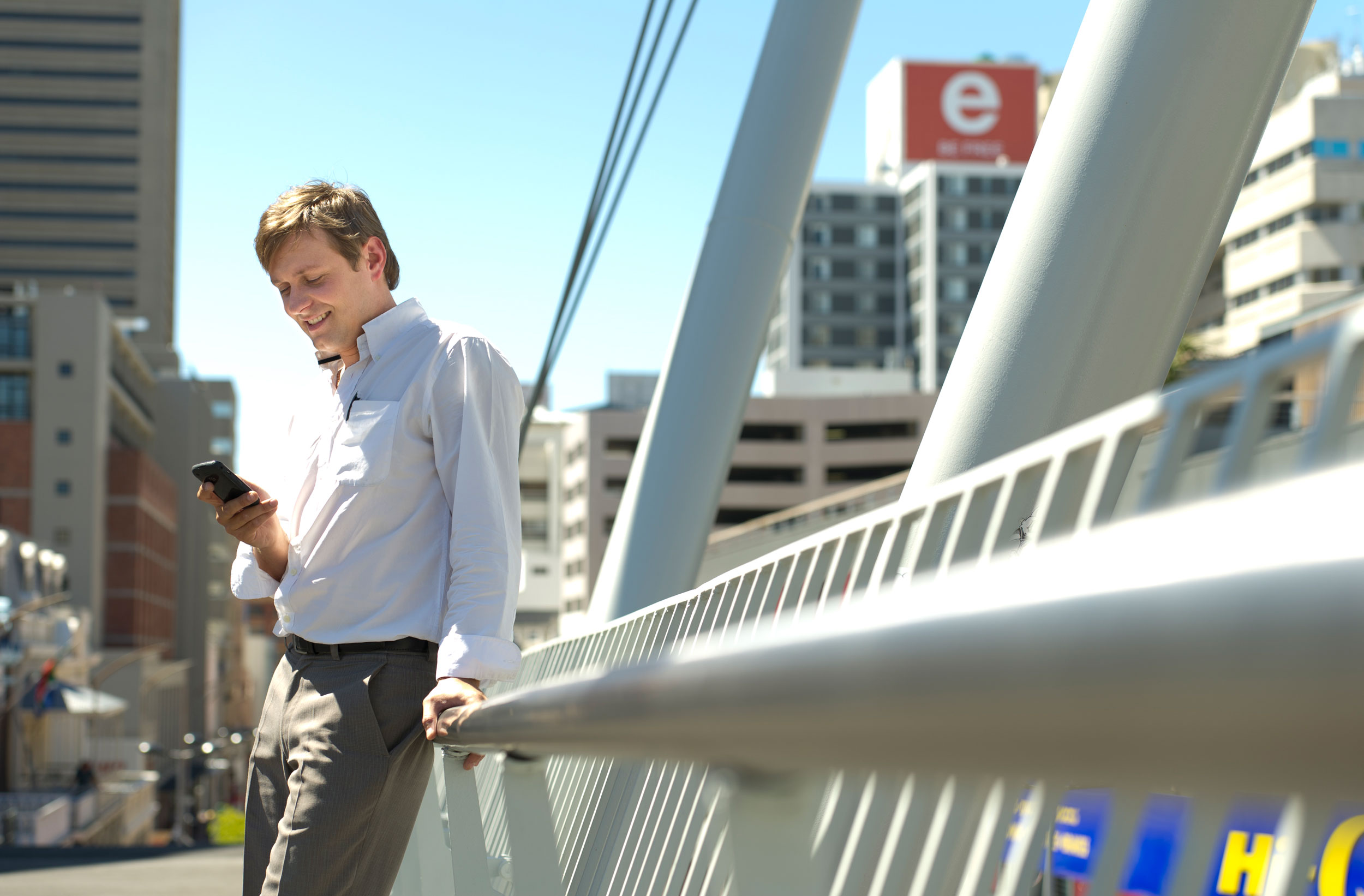 Guy on a bridge watching his mobile phone unretouched