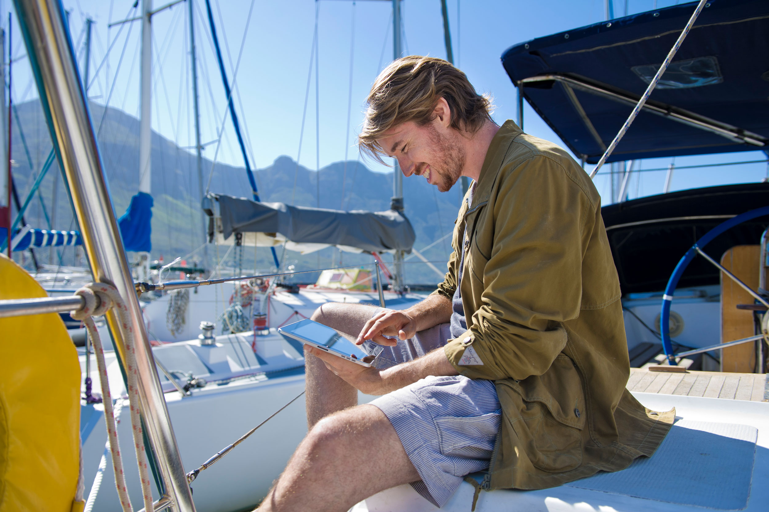 Guy on a boat is reading something on a iPad unretouched