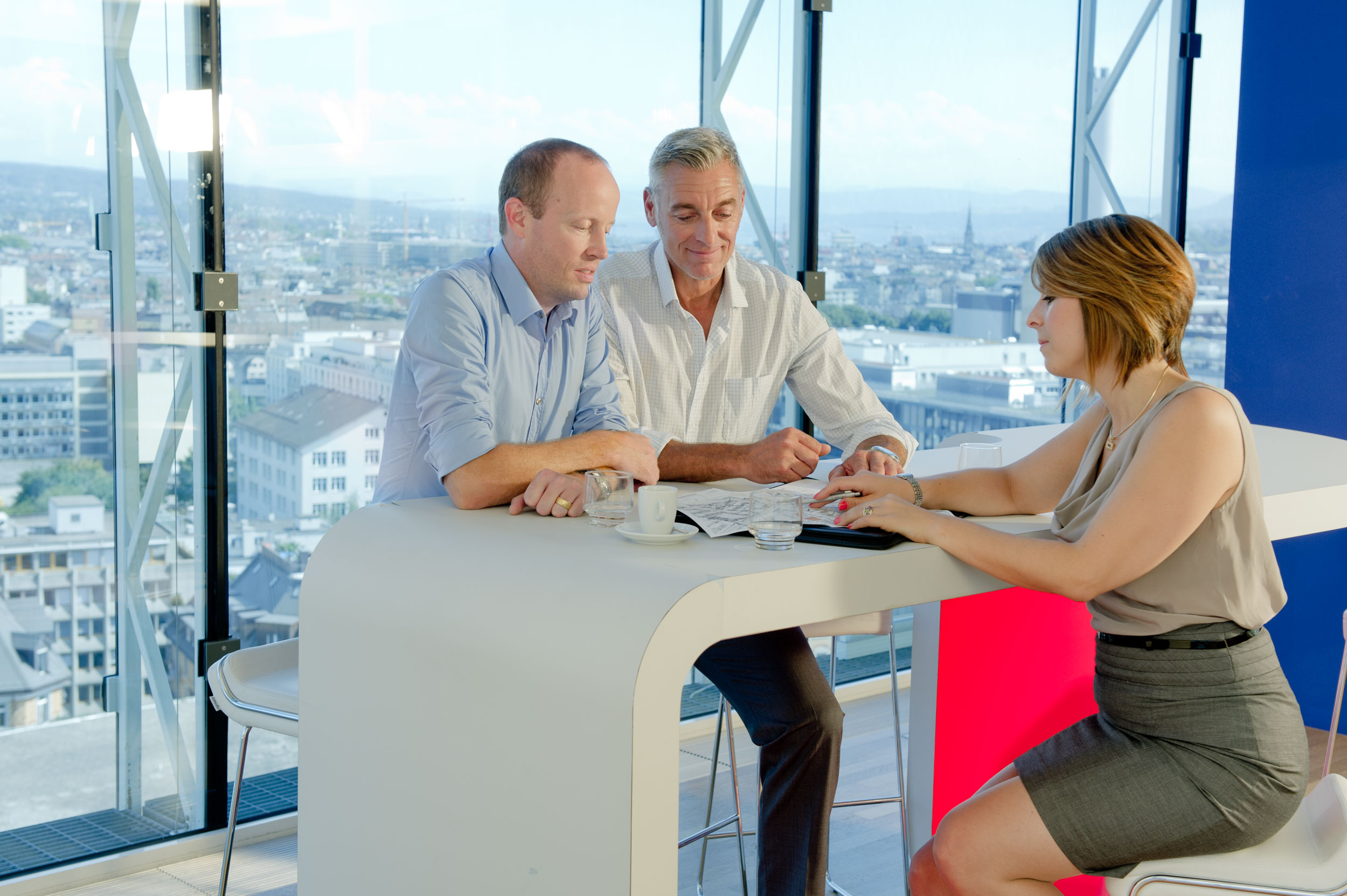 three person having a conversation in an office unretouched